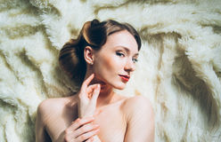 Beautiful portrait of young girl in retro style. On fur, looking to the camera, fingers near face Stock Photo