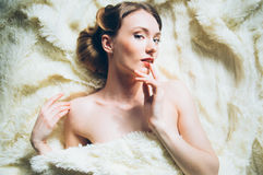 Beautiful portrait of young girl in retro style. On fur, looking to the camera, fingers near face Stock Photos