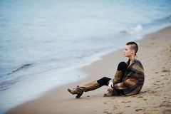 Beautiful portrait of young glamorous woman with short hair in leather boots and a knitted cardigan sitting on the beach looking a. T the waves Royalty Free Stock Images