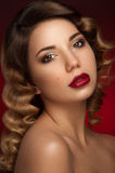 Beautiful portrait of young lady with brown eyes. Dark brown eye-shadows and deep red lipstick, two nevus on her right cheek and curly hair. Red background Stock Photos