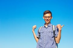 Beautiful portrait of a young man with glasses on a blue sky background royalty free stock photo