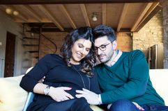 Beautiful portrait of young pregnant couple. Caressing mother s belly on yellow sofa Royalty Free Stock Photos