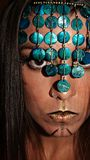 Beautiful portrait of a young woman looking at the camera with a gold and brown make up design covering her face with a turquoise stock photo
