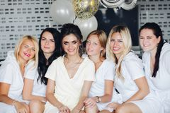 Beautiful and positive bide mades having fun on hen party. Company of beautiful and positive bide mades in bathrobes sitting on bed in hotel and shaking by stock photo