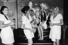 Beautiful and positive bide mades having fun on hen party. Company of beautiful and positive bide mades in bathrobes sitting on bed in hotel and shaking by royalty free stock photo