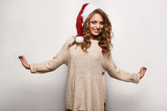 Beautiful positive blonde in a sweater and festive cap Stock Photos