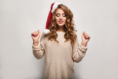 Beautiful positive blonde in a sweater and festive cap Royalty Free Stock Photos