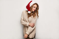 Beautiful positive blonde in a sweater and festive cap Royalty Free Stock Photography