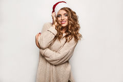 Beautiful positive blonde in a sweater and festive cap Royalty Free Stock Photo