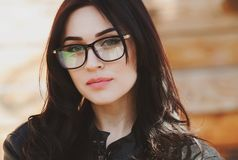 Beautiful positive fashionable stylish modern brunette girl in trendy glasses looking at camera