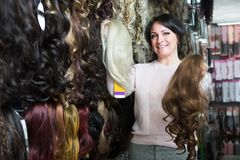Positive female customer selecting clip-in hair extension at sho. Beautiful Positive female customer selecting clip-in hair extension at shop Royalty Free Stock Images