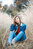 Beautiful positive girl in denim clothes sitting in autumn grass Stock Photos