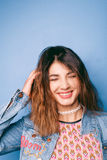 Beautiful positive girl in a jeans jacket on a blue background smiling and posing Royalty Free Stock Image