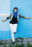 Beautiful positive woman posing in front of a blue wall Royalty Free Stock Photography