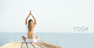 Beautiful positiveblond girl practicing yoga at. Beautiful blond woman practicing yoga at seashore and meditating Stock Photo