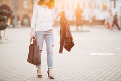 Brunette woman in hat walking at sunset after shopping.