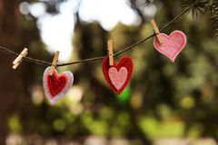 Beautiful postcard with red and pink hearts hanging stock photo