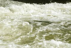 Beautiful powerful rapid steam of the mountain river flows between pebbles rocks. stock photo