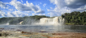 Beautiful powerful waterfall flowing into the lake. On a bright sunny day Royalty Free Stock Photos