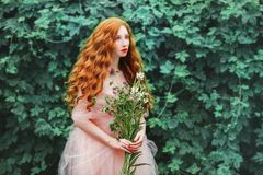 Beautiful pre-raphaelite girl with curly red hair with a flying tulle dress. On the background of a fern stock photos