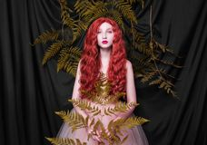 Beautiful pre-raphaelite girl with curly red hair with a flying tulle dress royalty free stock images