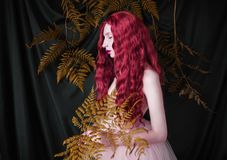 Beautiful pre-raphaelite girl with curly red hair with a flying tulle dress. On black background stock image