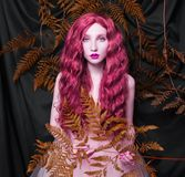 Beautiful pre-raphaelite girl with curly red hair with a flying tulle dress. On black background stock images