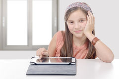 Beautiful pre-teen girl with a tablet computer. A beautiful pre-teen girl with a tablet computer Royalty Free Stock Photography
