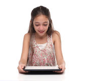 Beautiful pre-teen girl with a tablet computer. Isolated. Clipping path for the screen Royalty Free Stock Image