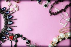 Beautiful precious shiny jewelery trendy glamorous jewelry set, necklace, earrings, rings, chains, brooches with pearls. And diamonds on a pink purple stock image