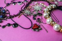 Beautiful precious shiny jewelery trendy glamorous jewelry set, necklace, earrings, rings, chains, brooches with pearls. And diamonds on a pink purple royalty free stock photography
