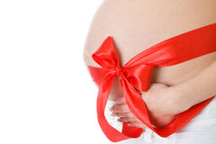 Beautiful pregnancy. Red christmas ribbon on a beautiful stomach of the pregnant woman Stock Photos