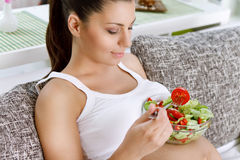 Beautiful pregnancy eating salad Stock Images
