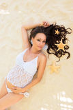 Beautiful pregnancy. Pregnant girl lying on a sandy beach with sea stars in her hair. Stock Image