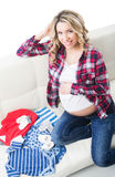 Beautiful pregnant blond with children's wear Stock Photos