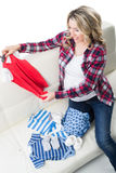 Beautiful pregnant blond with children's wear Royalty Free Stock Image