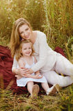 Beautiful pregnant blonde smiling mother and daughter hugging, family values, love Stock Images