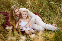Beautiful pregnant blonde smiling mother and daughter hugging, family values, love Stock Photo