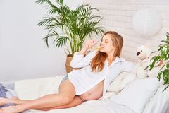 Beautiful pregnant blonde woman lying on the bed in a bright bedroom. girl on a large term pregnancy sipping fruit juice, natural royalty free stock photo