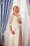 Beautiful pregnant bride posing against window Royalty Free Stock Photos