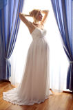 Beautiful pregnant bride posing against window Royalty Free Stock Images