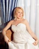 Beautiful pregnant bride posing against window Stock Image