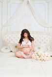 Beautiful pregnant brunette sitting on a bed in the lotus position Stock Images