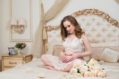 Beautiful pregnant brunette sitting on a bed in the lotus position royalty free stock photography