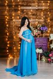 Beautiful pregnant brunette woman in a long silk blue dress standing at full height and looks at the belly. Beautiful pregnant brunette woman in a long silk blue royalty free stock photos