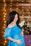 Beautiful pregnant brunette woman in a silk blue dress standing and looks at the belly in studio. Pregnant woman holding hands on her stomach stock photo