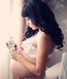 beautiful pregnant brunette woman with teddy bear Stock Photos