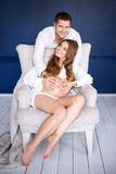 Beautiful pregnant couple happy together expecting a child. Studio portrait. Stock Images