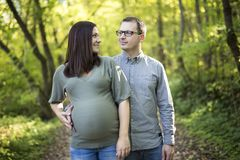 Beautiful pregnant couple relaxing outside in the park. Stock Photo