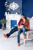 Beautiful pregnant couple relaxing on sofa at home together. Happy family, man and woman expecting a child. Stock Photography
